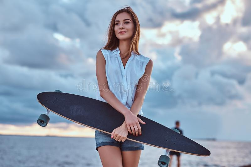 Sensual brunette girl dressed in shorts and a white shirt holds skateboard on the beach in cloudy weather during sunset. royalty free stock photos