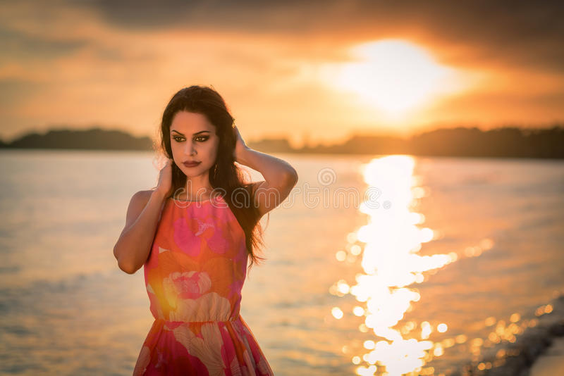 Sensual brunette with sea sunset background royalty free stock image