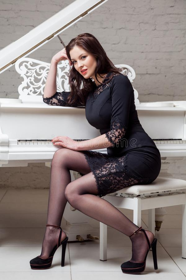 Sensual brunette woman in lace black classic dress sitting near white piano, posing and looking at camera and smiling stock photos