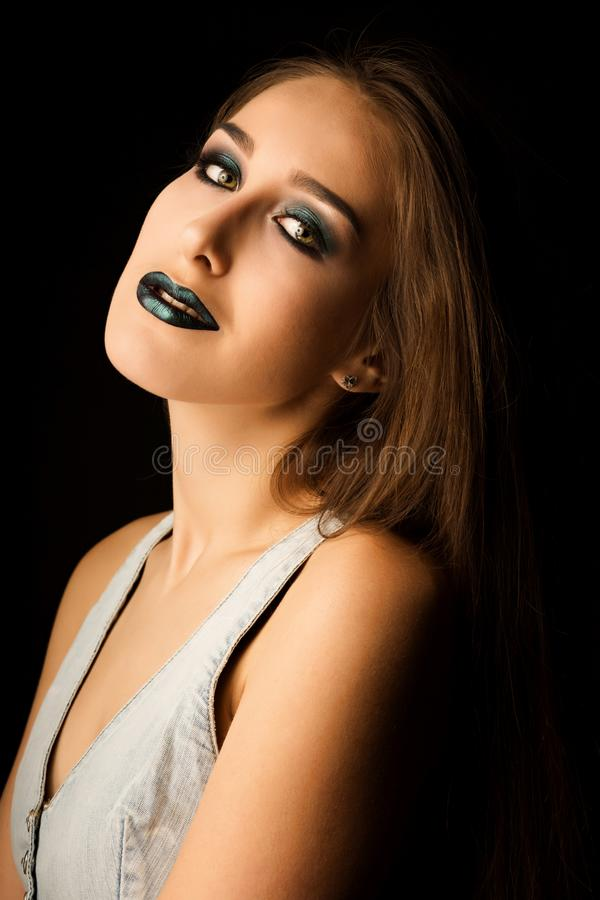 Sensual young model with perfect skin and creative metallic green makeup. Closeup portrait at studio on a dark background royalty free stock photos