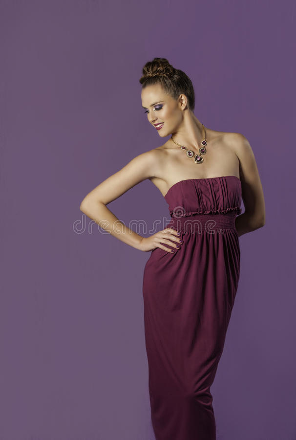 Sensual brunette woman posing in purple dress and makeup royalty free stock photography