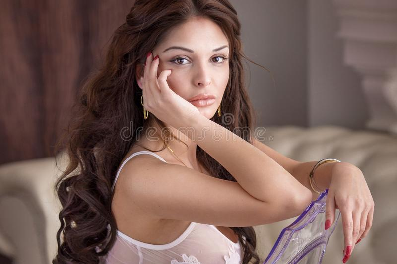 Sensual brunette woman sitting on chair royalty free stock images