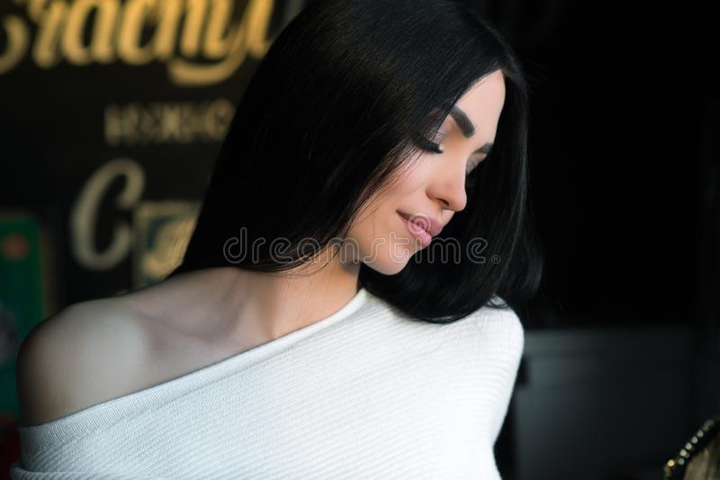 Sensual brunette woman in white sweater sits in cafe royalty free stock photo