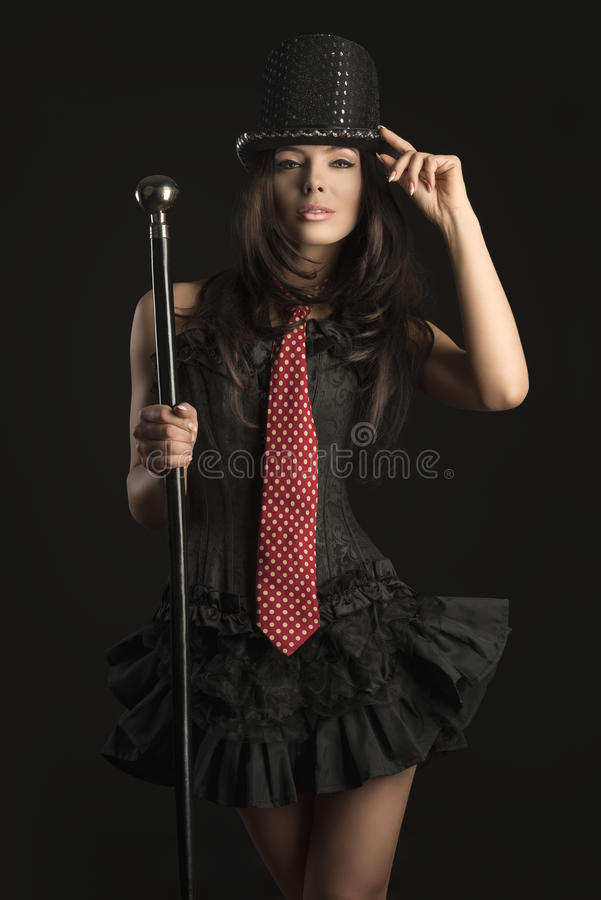 Sensual cabaret actress. Cabaret female actress with black corset, red tie, hat and brown hair taking stick in the hand in sensual pose royalty free stock image