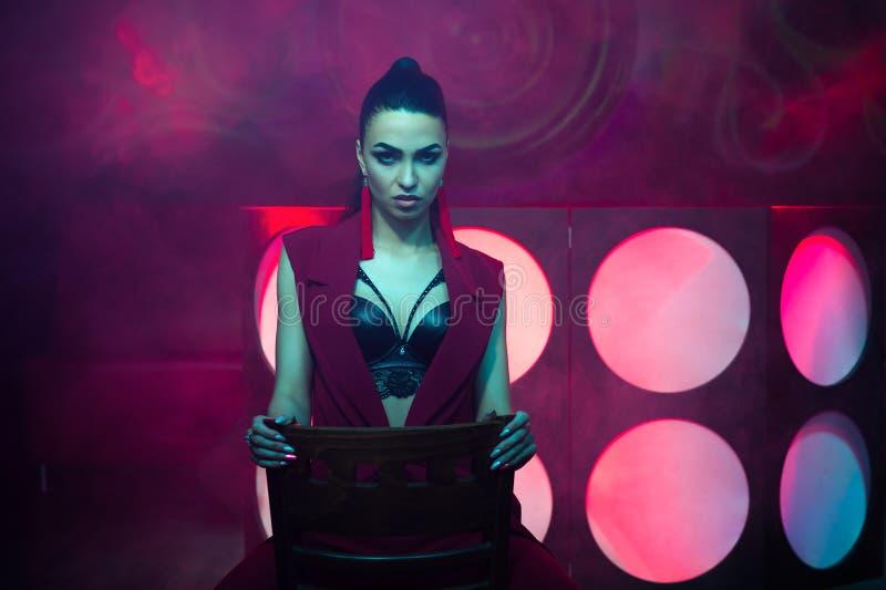 Sensual charming woman sitting on chair on dance floor stock photos