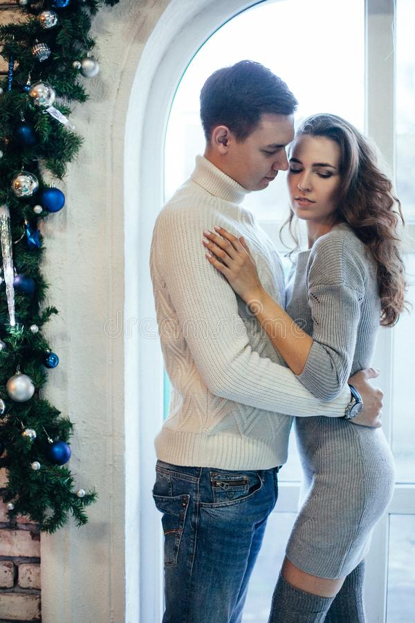 Romantic couple kissing and hugging in cosy sweaters near Christmas decoration stock image