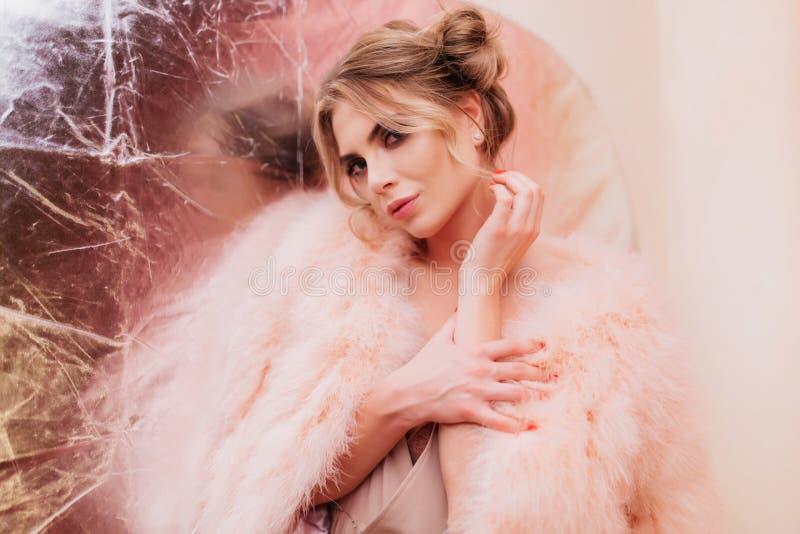 Sensual curly Girl in trendy rosa Pelzmantel sieht coquetschig aus und berührt ihre Hand Porträt von Adorable Blonde jung stockbild