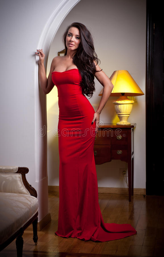 sensual elegant young woman in red dress and indoor shot. Black Bedroom Furniture Sets. Home Design Ideas