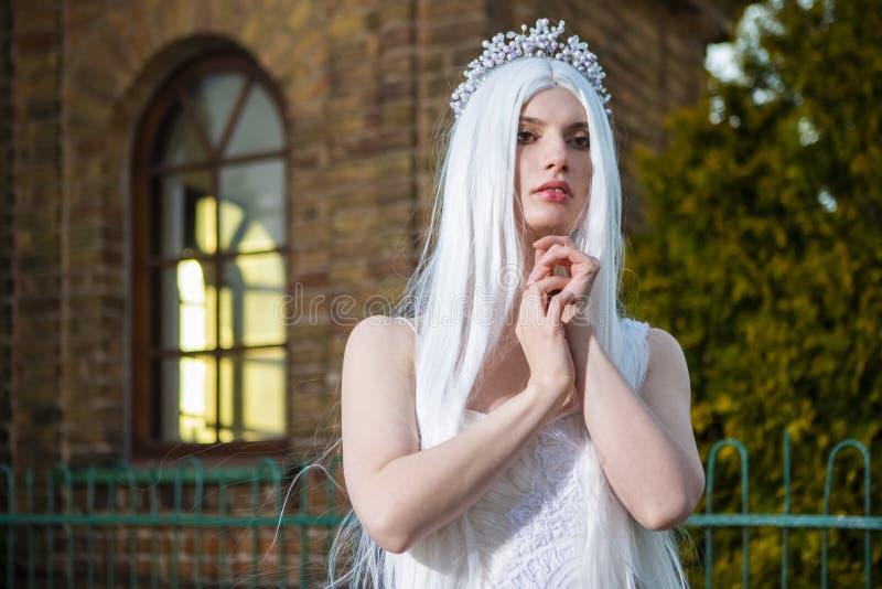 Sensual entspannte kaukasische Braut mit Tiara und langem Weißen Haar vor antikem Gebäude im Freien stockfotografie