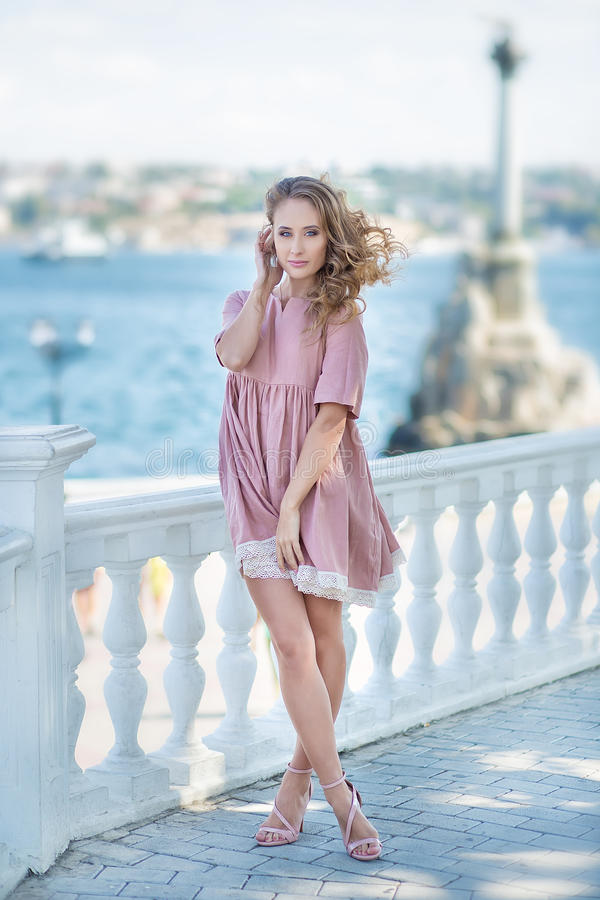 Sensual fascinating sunny portrait of stunning gorgeous elegant woman posing in downtown of european city. Classic white royalty free stock images