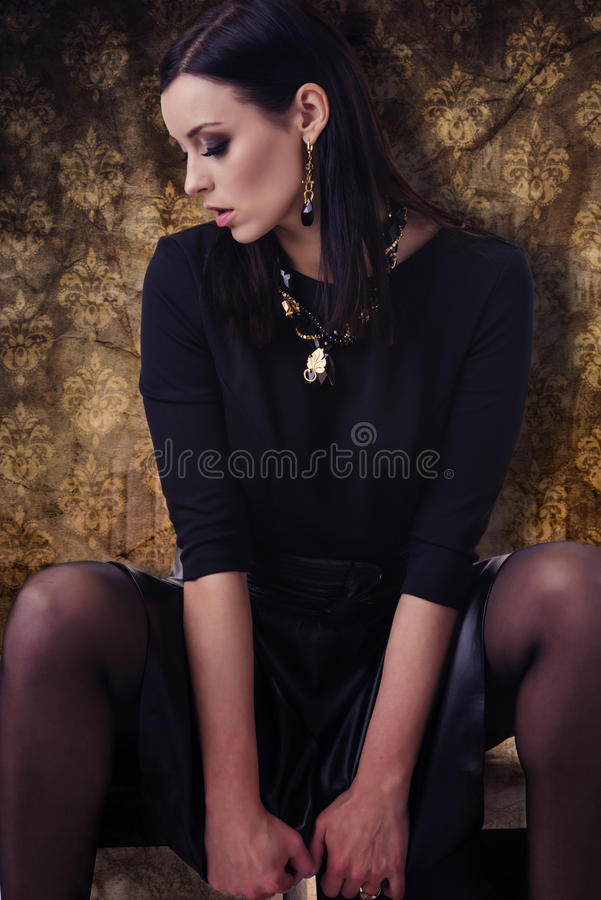 Sensual fashion model in black clothes with jewellery over golden pattern background. Beautiful, gorgeous brunette woman dressed in black shirt, black skirt stock images
