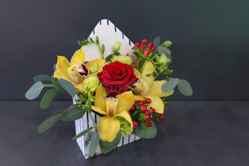 Sensual floral arrangement of exotic flowers in a box - an envelope. On a dark background stock photo