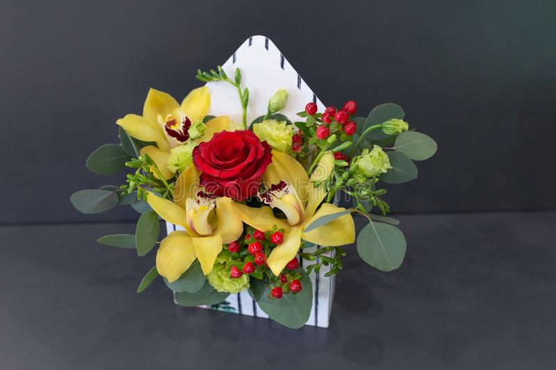 Sensual floral arrangement of exotic flowers in a box - an envelope. On a dark background royalty free stock photo