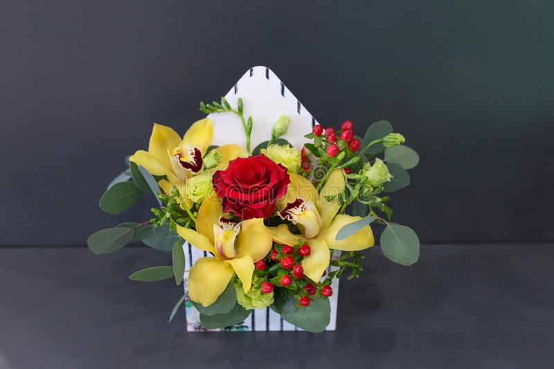 Sensual floral arrangement of exotic flowers in a box - an envelope. On a dark background stock photos