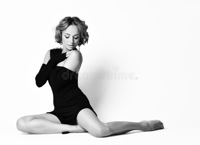 Sensual Frau in Schulterkleid sitzt in einer Tanzposium auf dem Boden, mit den Händen an ihrer Brust überkreuzt Portrait von sin lizenzfreie stockbilder