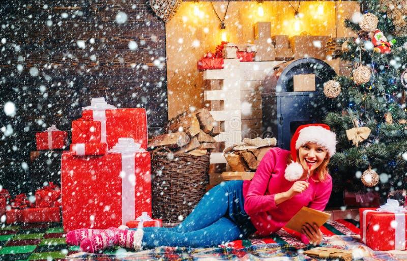 Sensual girl for Christmas. Blonde Santa woman holding gift box at vintage wall. Woman in red Santa hat holding present royalty free stock photos