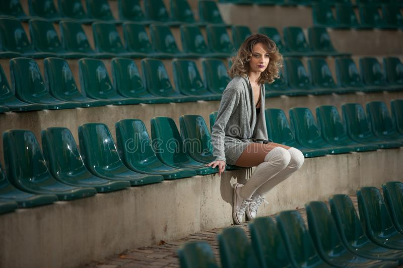 Sensual girl with long legs in the courts of a field .Long legs attractive blonde with curly hair relaxing on the chair. In the stands.Fashionable young woman stock photo