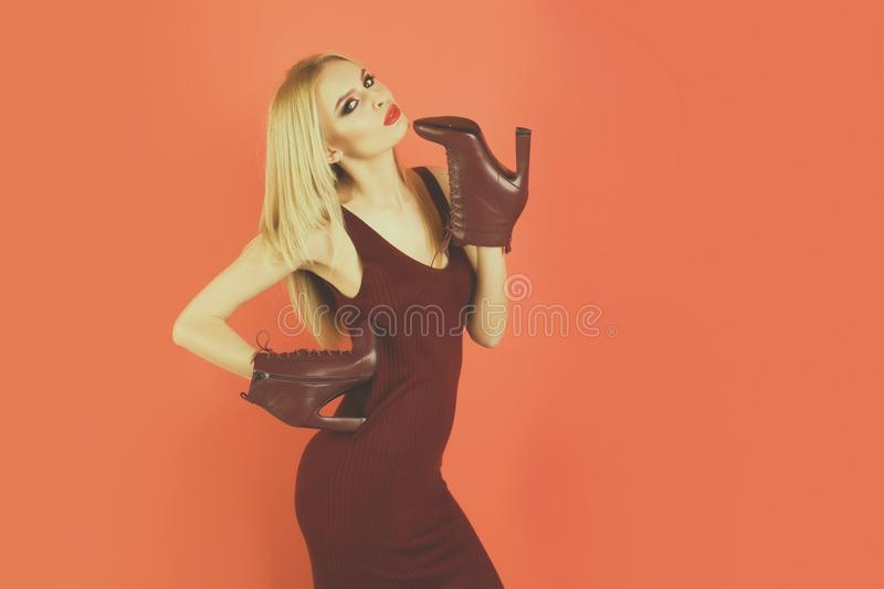 Beautiful woman with blonde hair, makeup, holds leather shoes. Sensual glamour portrait of beautiful woman model with makeup has red lips color and clean healthy stock photo