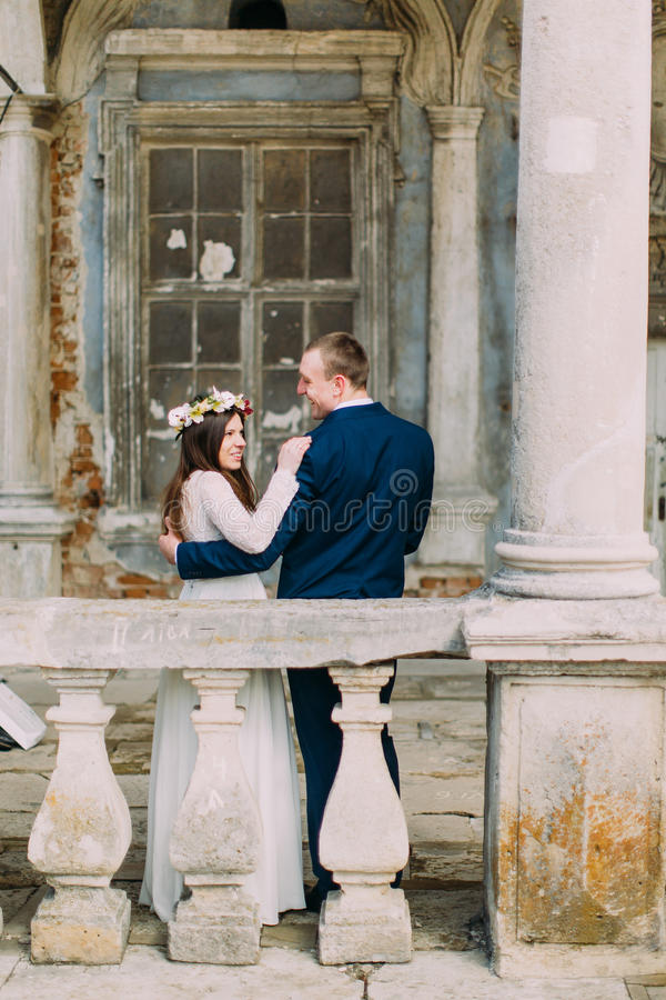 Sensual husband and wife hugging near balustrade in antique ruined palace. Back view royalty free stock photography