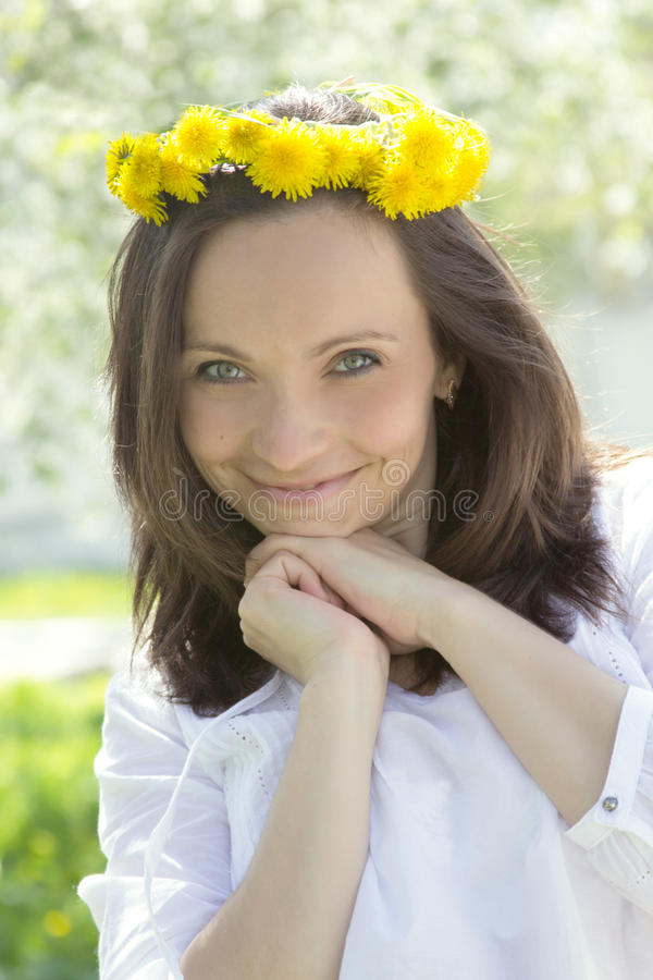 Sensual lovely woman with dandelion wreath. In spring stock images