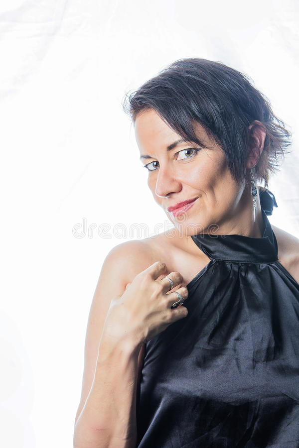 Sensual mature brunette. Mature woman in her 40s in shining black formal dress royalty free stock photography