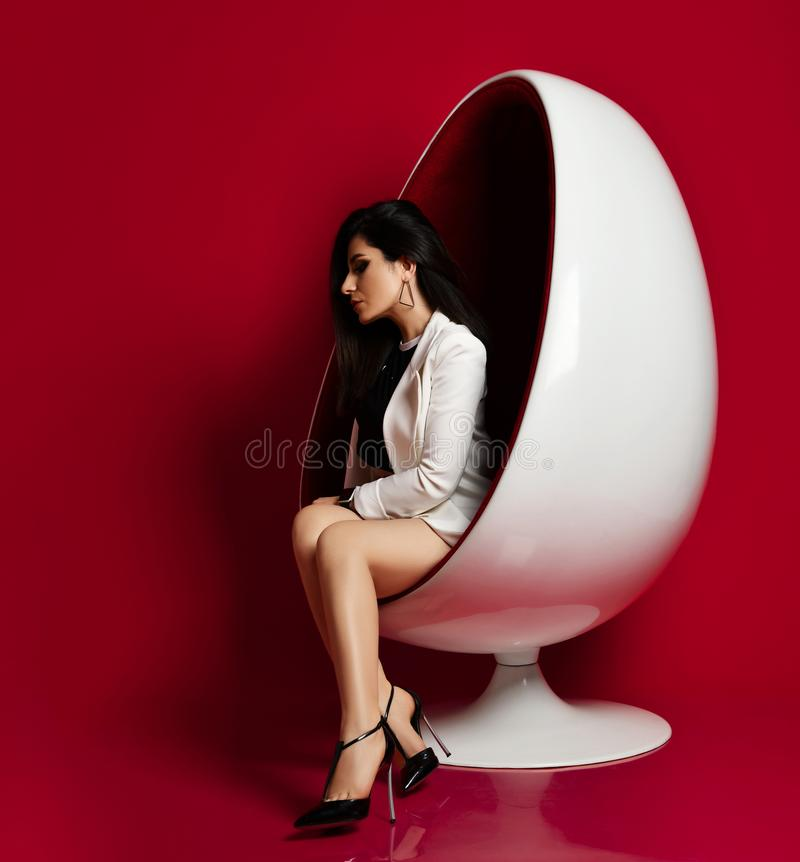 Sensual melancholic lady sexy brunette in white long jacket and high-heeled shoes sitting posing in a modern oval chair on red stock photography