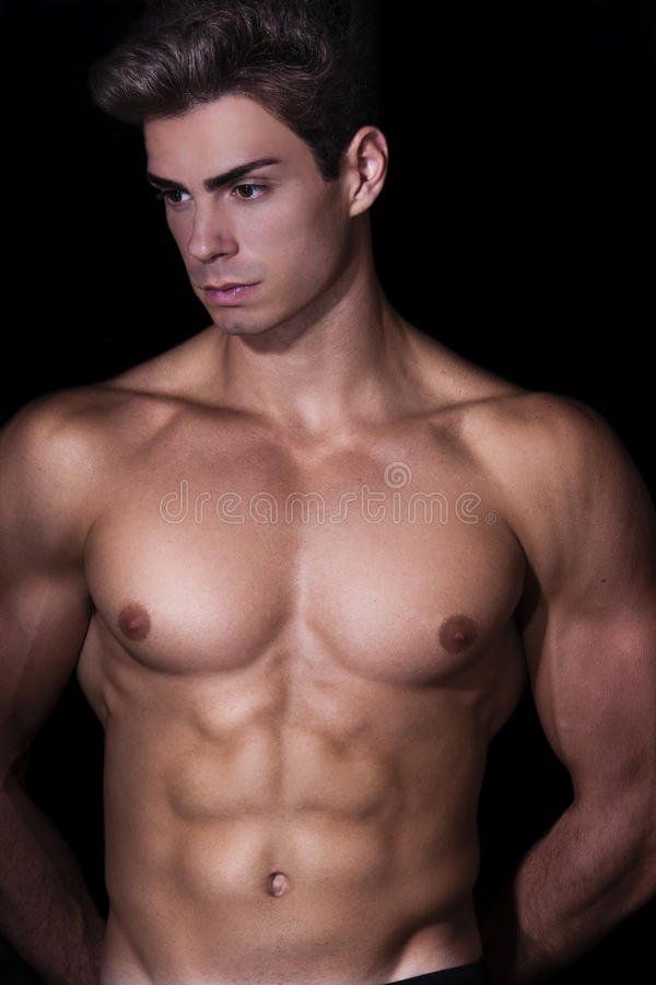 Sensual, muscular young man model. Hair style. Black background. A muscular man and beautiful young model is posing in studio. He has a statuesque body and its stock images