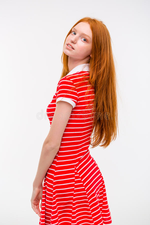 Sensual natural thoughtful girl with long red hair. Sensual natural tender candid thoughtful girl in red striped dress with long red hair posing on white royalty free stock photos