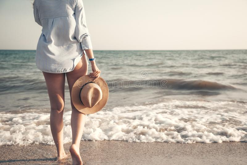 Sensual photo of barefoot girl with straw hat in her hand. Girl in shirt goes towards the sea or ocean. Evening on the royalty free stock photos