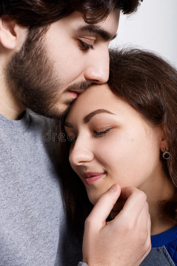 A sensual photo of loving couple standing close to each other. A young woman leaning to her boyfriend. A bearded hipster touching stock images