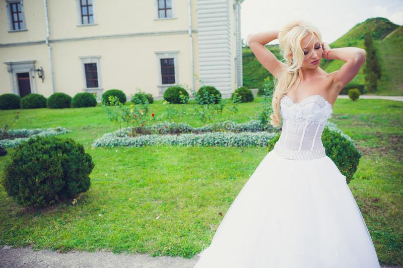Beautiful bride walking in the park near castle royalty free stock photo