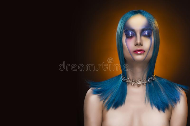 Sensual portrait of beautiful dyed blue hair naked shoulders closed eyes girl wearing necklace. Vanguard fashion make-up. royalty free stock images