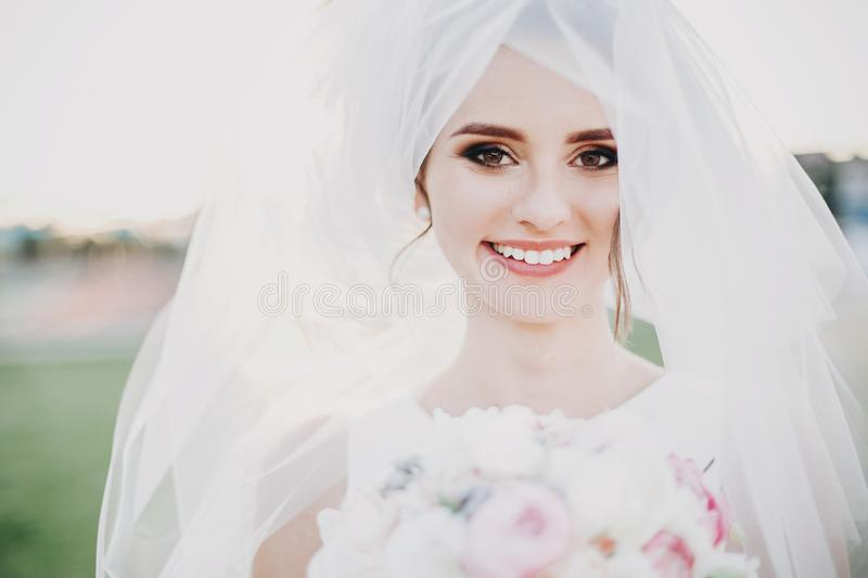 Sensual portrait of beautiful happy bride smiling under veil holding bouquet outdoors. Gorgeous bride in white gown with modern royalty free stock photo