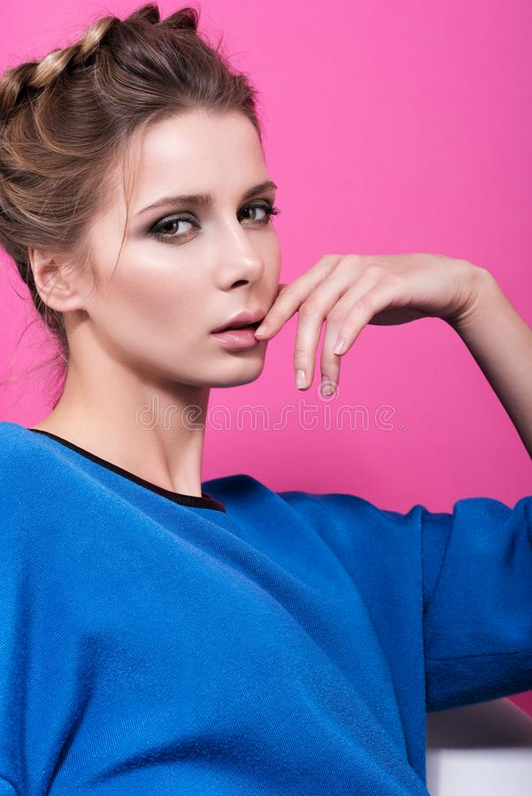 Sensual portrait of beautiful young woman in a blue sweater. Gentle touch fingers to face. Hair and light makeup. Bright pink background stock image