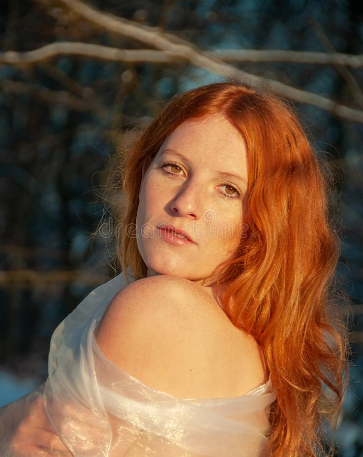 Sensual portrait of red-haired woman under the trees royalty free stock images