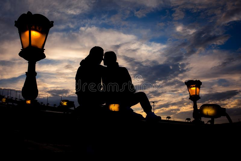 Sensual portrait of silhouette couple softly rubbing noses while sitting on the Chain Bridge near lightning street lamp royalty free stock image