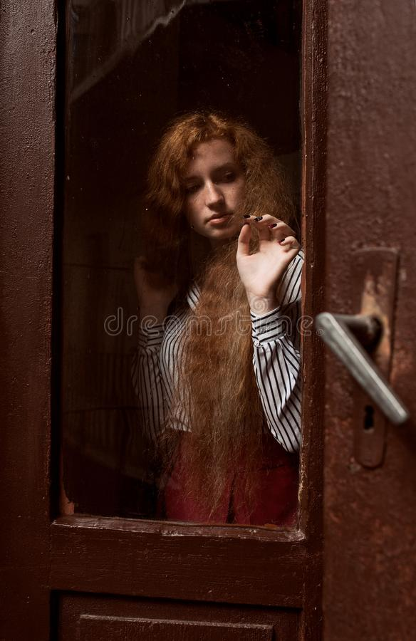 Sensual red haired model standing behind a closed glass door. Ra royalty free stock image