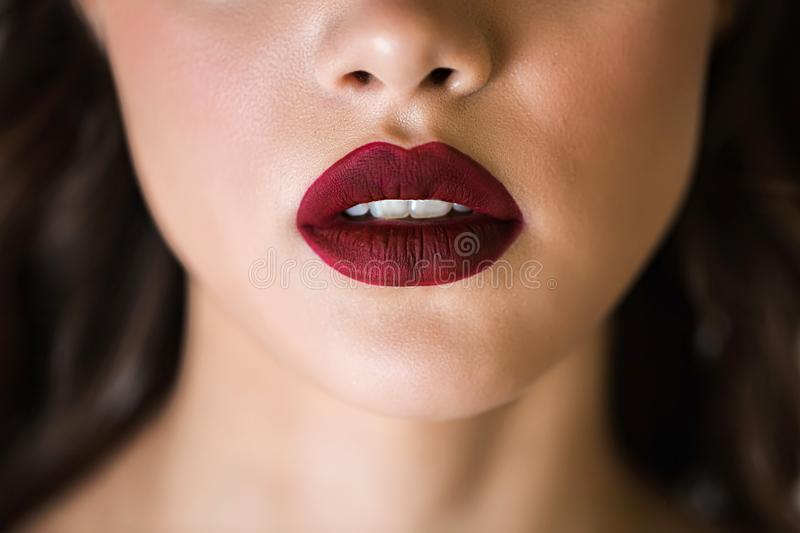 Sensual red woman lips. Half open lips. Close up face of a woman with clean skin. The concept of cosmetics, care, beauty, royalty free stock images