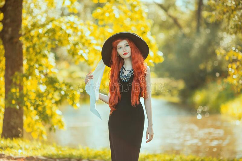 Sensual redhead girl in black retro dress on nature background. Beautiful vintage woman. Sensual lady in retro hat. Fashion stock photography
