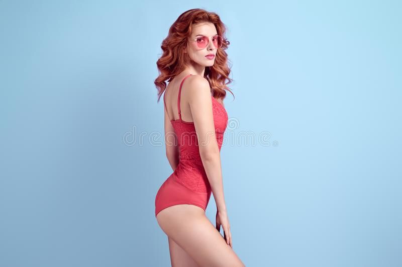 Sensual Redhead woman in bodysuit. Fashion Outfit. Fashionable shapely Redhead woman with make up wearing Stylish Coral bodysuit. Beautiful fitness Lady in royalty free stock images