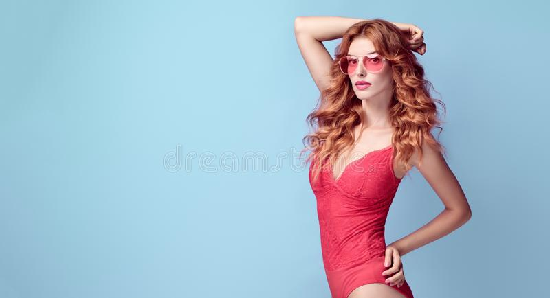 Sensual Redhead woman in bodysuit. Fashion Outfit. Graceful Curly Redhead woman with make up wearing Stylish Coral bodysuit. Beautiful fitness Lady in Trendy royalty free stock photo