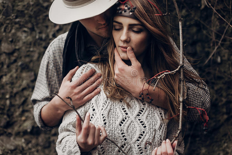 Sensual romantic man in cowboy hat hugging a beautiful gypsy brunette woman from behind, while she is holding a berry tree branch royalty free stock photography