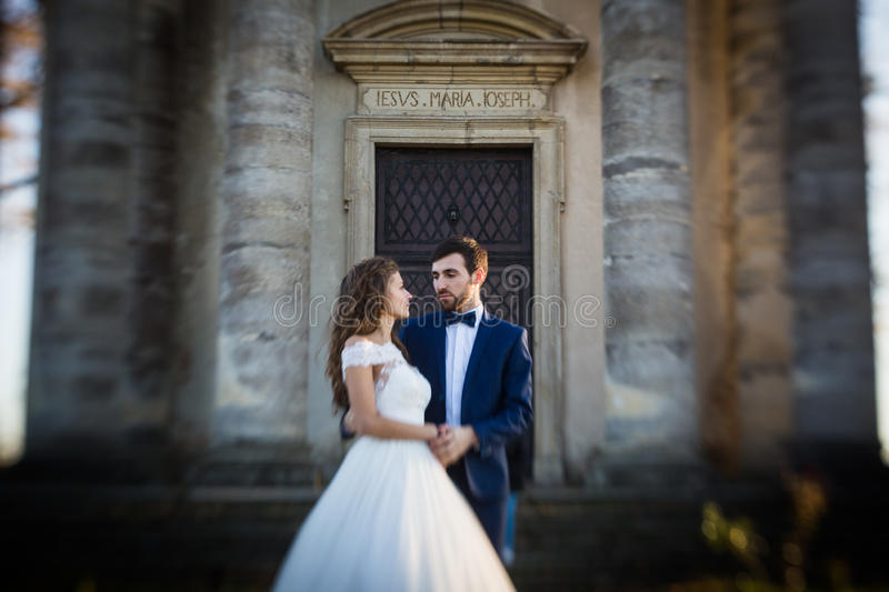 Sensual romantic newlywed bride and groom hugging in front of old baroque church stock image