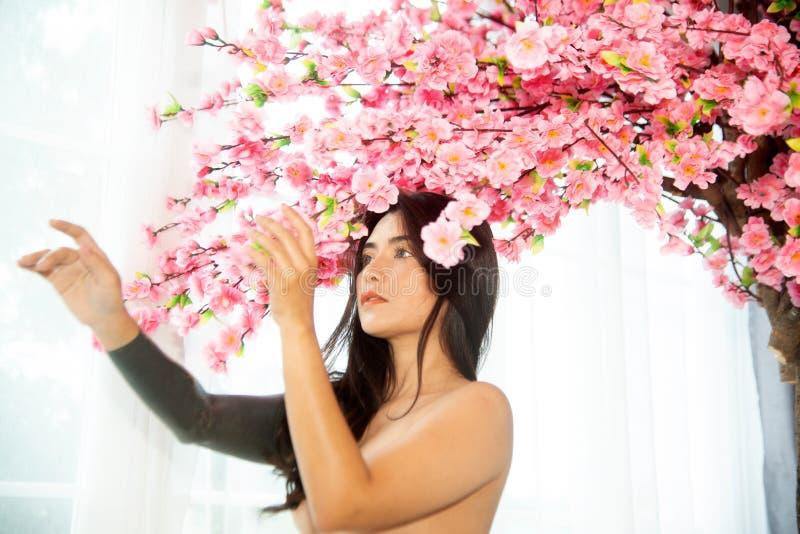 Sensual sexy Asian women sensuality standing under pink flower tree near window. Sensual pretty sexy Asian woman sensuality standing under pink flower near royalty free stock photos
