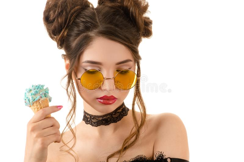 Sensual brunette woman in round glasses with ice cream in hand royalty free stock photos