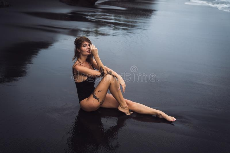 Sensual sexy girl in swimsuit with wet hair sits on black sand beach royalty free stock photography