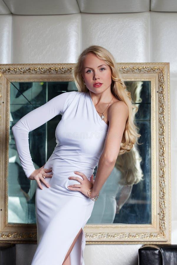 Sensual slim blonde posing in front of mirror stock image