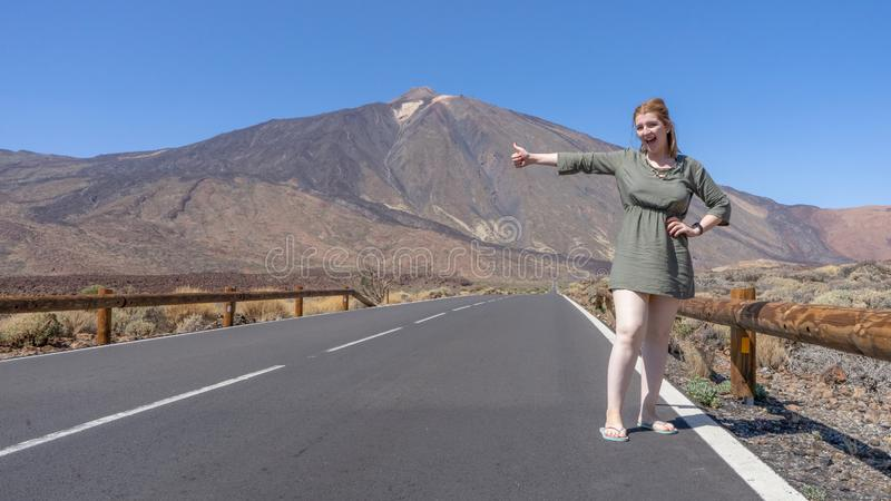 Sensual solo traveler blond girl catching a transportation in the volcano of Tenerife, el Teide in Canary Islands in a lonely road royalty free stock photography