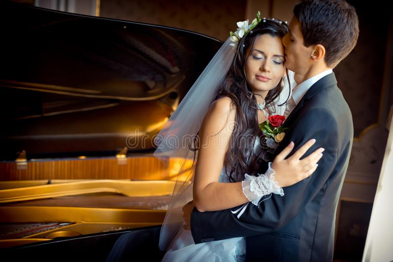 Sensual wedding portrait. The handsome groom is tenderly kissing his beautiful bride in the forehead at the background stock photo