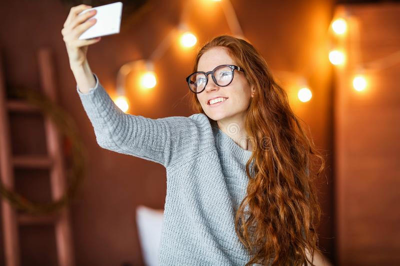 Sensual white girl with wavy hairstyle making selfie in morning. Attractive young woman lying on bed and taking picture stock image